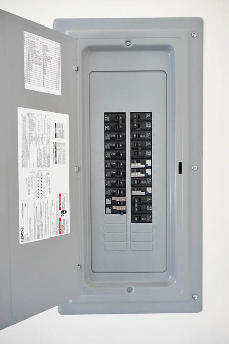This picture shows an electrical panel installation in Pasadena after an upgrade from a old fuse box. It is a new circuit breaker with the door open showing the breakers.